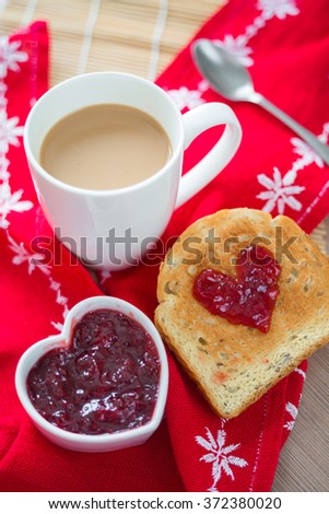 Toast with strawberry jam in a heart shape. Valentine's Day cofee with milk