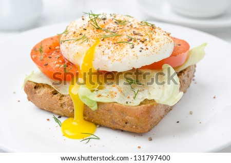 toast with tomato, lettuce and poached egg on a white plate for breakfast closeup