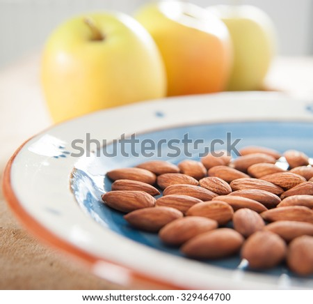 Toasted almonds on terra cotta painted dish with three golden delicious apples on the background - stock photo