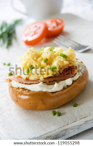 Toasted bagel with ham, cream cheese, chives and scrambled egg topping - stock photo