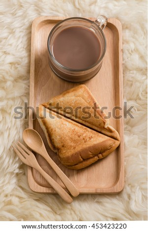 Toasted bread and hot drink / wooden plate spoon and folk / fluffy background