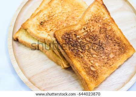 toasted bread on wooden plate isolated on white background