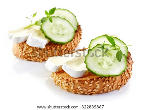toasted bread slice with brie and cucumber isolated on white background