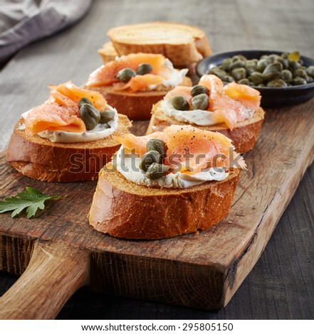 toasted bread slices with cream cheese and smoked salmon on wooden cutting board - stock photo