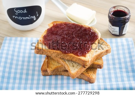 Toasted bread tower on a kitchen table with marmalade, butter and a tea mug with good morning sign. - stock photo