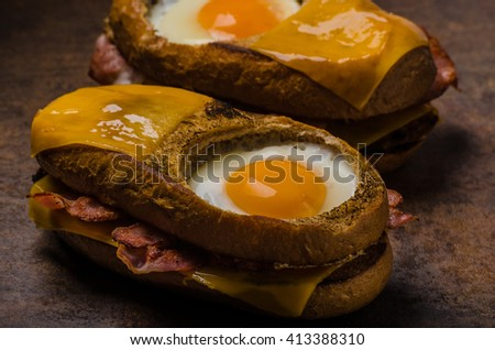 Toasted bread with cheddar cheese and crispy bacon, fried egg inside bread