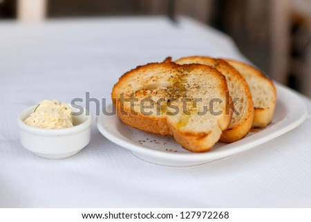 Toasted bread with garlic and spices on a white plate and butter - stock photo