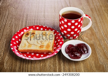 toasted bread with love message and raspberry jam and tea  .Breakfast for a loved one - stock photo