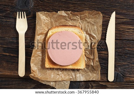 Toasted bread with sausage on dark wooden table, top view - stock photo