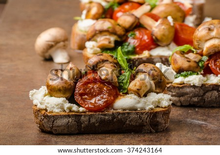 Toasted bruschetta with ricotta, basil pesto and cherry tomatoes, roasted mushrooms