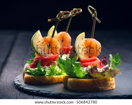 Toasted Canape with Shrimp and Salmon on dark background close-up