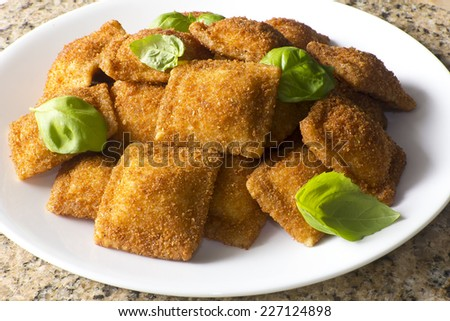 Toasted cheese ravioli garnished with fresh basil leaves - stock photo