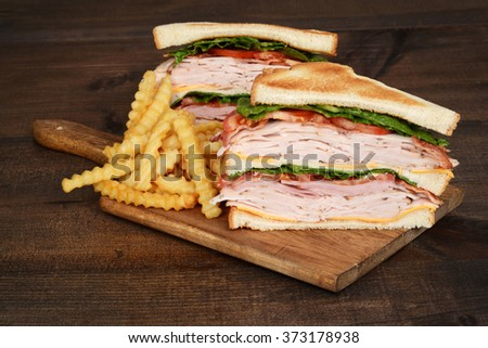 toasted chicken club sandwich with fries - stock photo