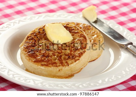 Toasted crumpets with butter on a red checked tablecloth