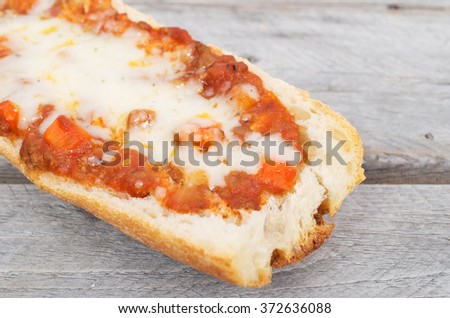 Toasted French baguette covered with meat sauce and cheese - stock photo