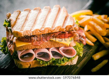 Toasted or grilled ham and cheese club sandwich with fresh lettuce and tomato and a side serving of potato chips, close up view - stock photo