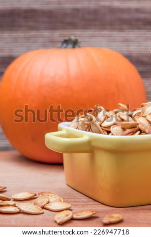 Toasted pumpkin seeds with a fresh pumpkin on a wooden cutting board - stock photo