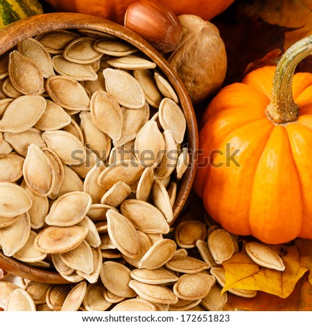 Toasted, salted pumpkin seeds spilling from a wooden bowl, accented with nuts and a small pumpkin