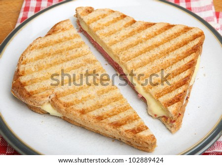 Toasted sandwich with beef pastrami and melting cheese - stock photo