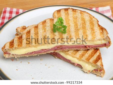 Toasted sandwich with beef pastrami and melting cheese. - stock photo