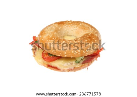 Toasted sesame seeded bagel filled with melted cheese,tomato,ham and basil isolated against white - stock photo