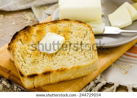 Toasted slices of freshly baked sourdough bread with butter. - stock photo