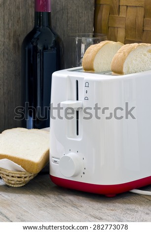 Toaster with bread slices on wooden table. - stock photo