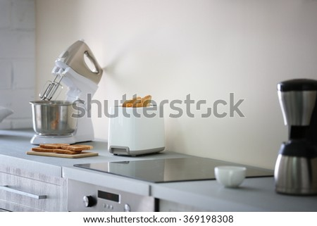 Toaster with coffee maker and mixer on a light kitchen table - stock photo