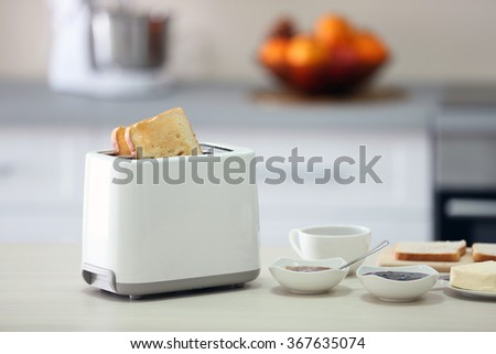 Toaster with dishes on a light kitchen table - stock photo