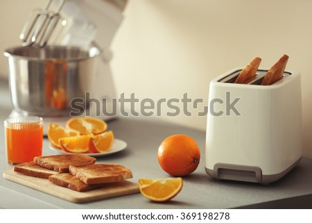 Toaster with mixer and oranges on a light kitchen table - stock photo