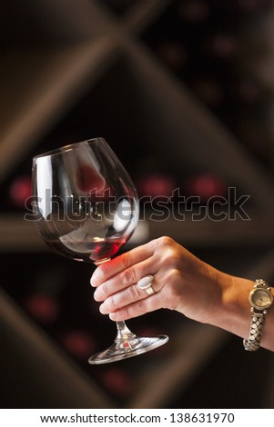 Toasting a wine glass in a wine cellar. - stock photo