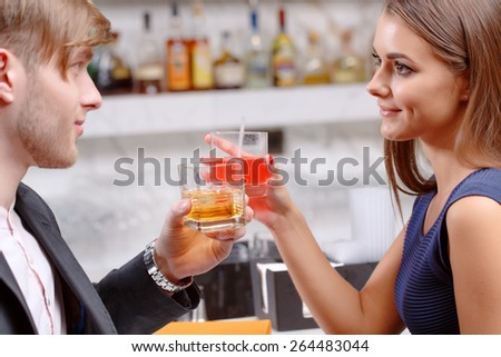 Toasting for love. Close-up of a young attractive couple holding glasses with drinks with bar counter on the background - stock photo