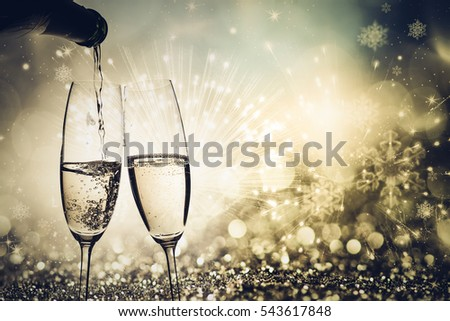 toasting with champagne glasses against holiday lights and new year fireworks