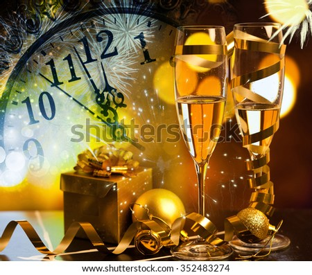 Toasting with champagne glasses against holiday lights, fireworks and clock at midnight