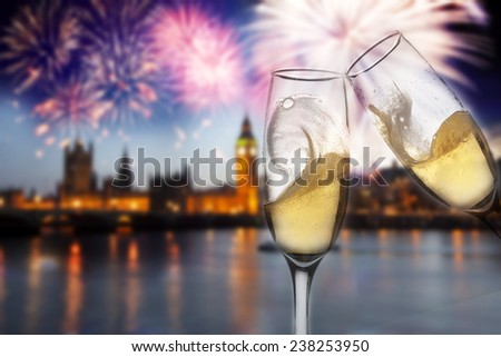 Toasting with champagne in London - Westminster abbey with fireworks in the background - stock photo