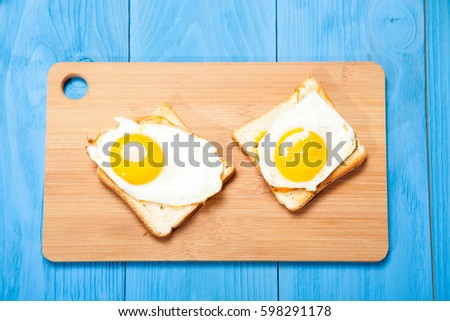 Toasts and egg on a blue wooden table