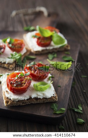 Toasts (Crostini) with ricotta and cherry tomatoes on wooden background - stock photo