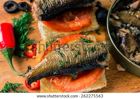 Toasts with a large smoked sardines. On the table hot peppers and olives
