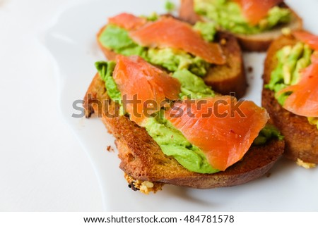 Toasts with avocado and smoked salmon on the white plate