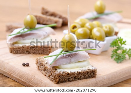 toasts with butter,cucumber, olives and salted herring,  selective focus - stock photo