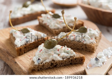 toasts with cheese pate and capers on a wooden board, close-up - stock photo