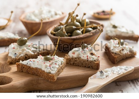 toasts with cheese pate and capers, selective focus, horizontal - stock photo