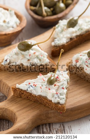 toasts with cheese pate and capers, vertical, close-up - stock photo