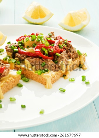 Toasts with mustard sauce, liver and stir-fry pepper. Shallow dof.