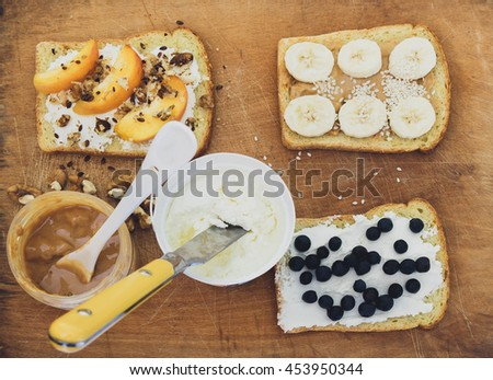 Toasts with peanut butter, cheese and fresh fruits on wooden background from top view