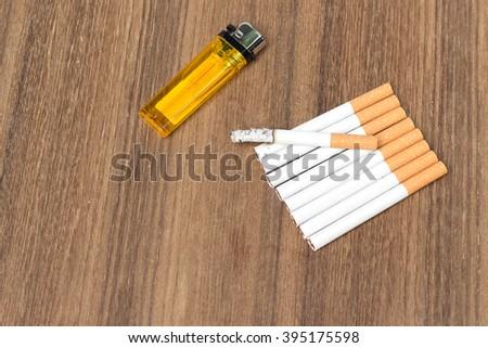 Tobacco and lighter,  burn cigarette detrimental on wood background ,select focus front  cigaretter - stock photo