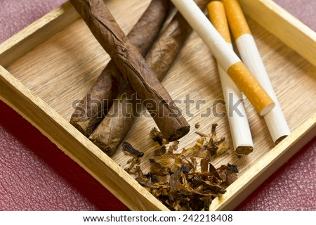 Tobacco, cigarettes, cigars, smoking, etc. on red leather background  - stock photo