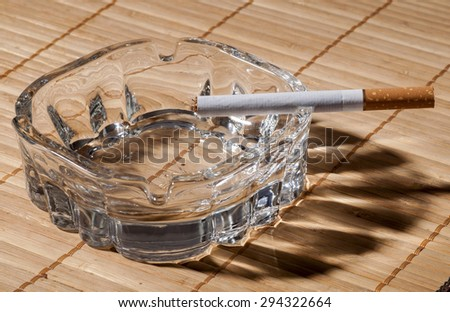Tobacco in cigarettes with brown filter and ashtray close up - stock photo