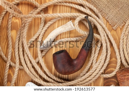 Tobacco pipe and rope on wooden background