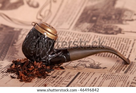 Tobacco pipe on old paper. Shallow depth of field. - stock photo